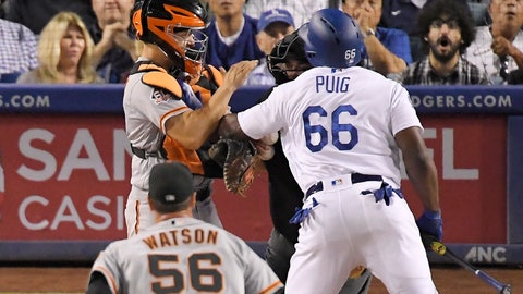 <p>               Los Angeles Dodgers' Yasiel Puig, right, shoves San Francisco Giants catcher Nick Hundley, left, as they argue while relief pitcher Tony Watson, below, runs in and home plate umpire Eric Cooper gets between them during the seventh inning of a baseball game, Tuesday, Aug. 14, 2018, in Los Angeles. (AP Photo/Mark J. Terrill)             </p>