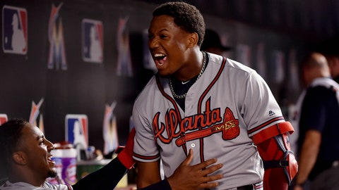 Aug 23, 2018; Miami, FL, USA; Atlanta Braves left fielder Ronald Acuna Jr. (C) reacts after hitting a solo home run with teammate Braves second baseman Ozzie Albies (left) in the dugout in the third inning at Marlins Park. Mandatory Credit: Steve Mitchell-USA TODAY Sports