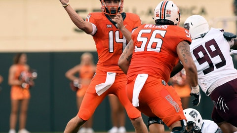 <p>               Oklahoma state quarterback Taylor Cornelius (14) throws a pass over teammate and offensive lineman Larry Williams (56) while under pressure from Missouri State defensive tackle Kylin Washington (99) during the first quarter of an NCAA college football game in Stillwater, Okla., Thursday, Aug. 30, 2018. (AP Photo/Brody Schmidt)             </p>