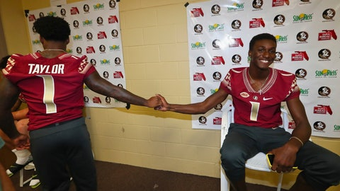 <p>               Florida State defensive back Levonta Taylor shakes hands with quarterback James Blackmon during the NCAA college football media day Sunday, Aug. 19, 2018, in Tallahassee, Fla. Both veteran players started fall camp wearing double digit numbers like the rest of the team, but earned their single digits back and wore them for the first time today. (AP Photo/Phil Sears)             </p>