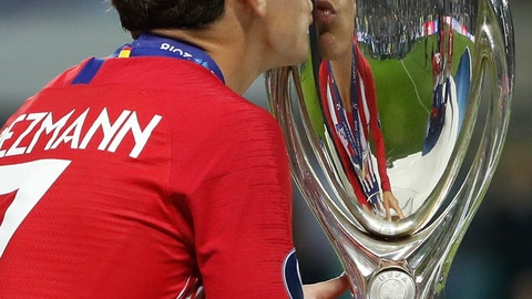 <p>               Atletico's Antoine Griezmann kisses the trophy after the UEFA Super Cup final soccer match between Real Madrid and Atletico Madrid at the Lillekula Stadium in Tallinn, Estonia, Wednesday, Aug. 15, 2018. (AP Photo/Pavel Golovkin)             </p>