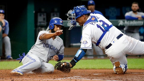Toronto Blue Jays' Richard Urena is tagged out by Kansas City Royals catcher Salvador Perez as he tried to score on a single by Randal Grichuk during the third inning of a baseball game.