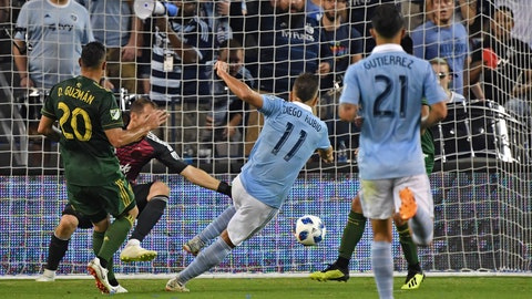 Aug 18, 2018; Kansas City, KS, USA; Sporting KC forward Diego Rubio (11) scores a goal past Portland Timbers goalkeeper Jeff Attinella (1) during the first half against at Children's Mercy Park. Mandatory Credit: Peter G. Aiken/USA TODAY Sports