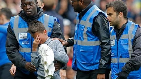 <p>               Security guards escort a crying boy who is holding the shirt PSG's Neymar gave him after he ran onto the pitch at the end of the French League One soccer match between Rennes and Paris-Saint-Germain at Roazhon Park stadium in Rennes, western France, Sunday, Sept. 23, 2018. (AP Photo/Michel Euler)             </p>