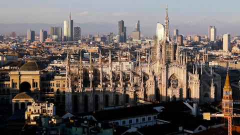 """<p>               FILE - In this Jan. 4, 2017 file phtoo, the pinnacles of the Duomo gothic cathedral are lit by the afternoon sun and backdropped by the new Business Center, in Milan, northern Italy. Italy's three-pronged bid for the 2026 Winter Olympics has been reduced to a two-city candidacy featuring Milan and Cortina d'Ampezzo. Following Turin's exclusion, the Italian Olympic Committee is sending a delegation featuring Milan and Cortina representatives to meet with IOC leaders on Wednesday to update the situation. The move comes after government undersecretary and sports delegate Giancarlo Giorgetti told the Senate on Tuesday that the three-pronged proposal """"is dead."""" (AP Photo/Luca Bruno, File)             </p>"""