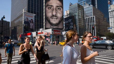 <p>               People walk by a Nike advertisement featuring Colin Kaepernick on display, Thursday, Sept. 6, 2018, in New York. Nike this week unveiled the deal with the former San Francisco 49ers quarterback, who's known for starting protests among NFL players over police brutality and racial inequality. (AP Photo/Mark Lennihan)             </p>