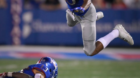 <p>               Kansas Jayhawks wide receiver Kwamie Lassiter II (83) goes high to avoid other players during a punt return against Nicholls State during the second half of an NCAA college football game in Lawrence, Kan., Saturday, Sept. 1, 2018. (AP Photo/Reed Hoffmann)             </p>