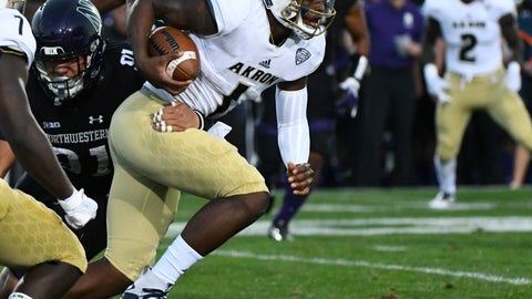 <p>               Akron quarterback Kato Nelson (1 runs against Northwestern defensive lineman Samdup Miller (91) during the first half of an NCAA college football game in Evanston, Ill., Saturday, Sept. 15, 2018. (AP Photo/Matt Marton)             </p>