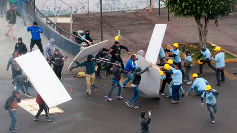 <p>               In this photo provided by the Andina government news agency, Alianza Lima club soccer fans, left, fight with members of an evangelical church, yellow helmets at right, outside the soccer club's stadium in Lima, Peru, Monday, Sept. 10, 2018. The two groups clashed outside the stadium over who has the right to use the area surrounding the sports venue, after the religious group arrived early in the morning and started removing the team's logos from the parking area. (Norman Cordova/Andina News Agency via AP)             </p>