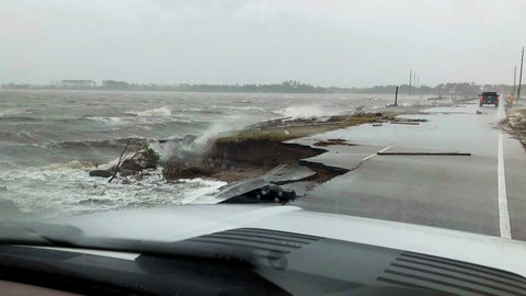 <p>               In this photo provided by Jordan Guthrie, wind and water from Hurricane Florence damages the highway leading off Harkers Island, N.C. on Friday, Sept. 14, 2018.  (Jordan Guthrie via AP)             </p>