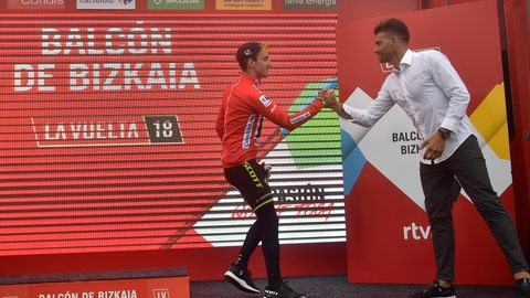 <p>               Mitchelton-Scott's Team Simon Yates of Great Britain, red shirt leader, is congratulated by La Vuelta staff member Oscar Pereiro at the end of the 17th stage between Getxo and Balcon de Vizcaya, 157 kilometers (97,55miles), of the Spanish Vuelta cycling race that finishes in Balcon de Vizcaya, northern Spain, Wednesday, Sept. 12, 2018. (AP Photo/Alvaro Barrientos)             </p>
