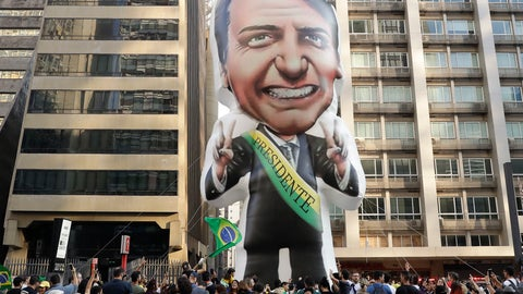 """<p>               FILE - In this Sept. 9, 2018 file photo, supporters of Jair Bolsonaro, presidential candidate for the National Social Liberal Party who was stabbed during a campaign event days ago, exhibit a large, inflatable doll in his image to show support for him, in Sao Paulo, Brazil. Silas Malafaia, one of Brazil's most influential pastors, visited Bolsonaro in the hospital. """"God is an expert in turning chaos into a blessing,"""" Malafaia said in a video he posted on YouTube from Bolsonaro's hospital room. (AP Photo/Andre Penner, File)             </p>"""