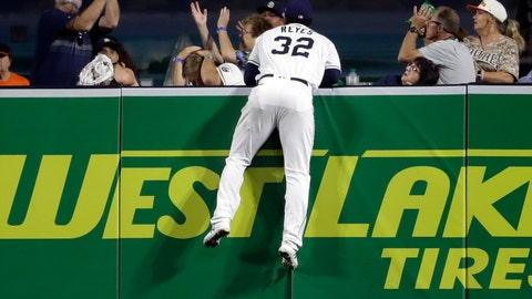 <p>               San Diego Padres center fielder Franmil Reyes (32) watches from the wall as a fan tries to catch a home run ball hit by the San Francisco Giants' Brandon Crawford during the fourth inning of a baseball game Monday, Sept. 17, 2018, in San Diego. (AP Photo/Gregory Bull)             </p>