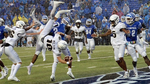 <p>               Central Florida quarterback McKenzie Milton (10) dives over Memphis defensive back's Josh Perry (4) and T.J. Carter (2) as he scores the go-ahead touchdown on a 7-yard run during the second half of an NCAA college football game Saturday, Oct. 13, 2018, in Memphis, Tenn. Central Florida won 31-30. (AP Photo/Mark Zaleski)             </p>