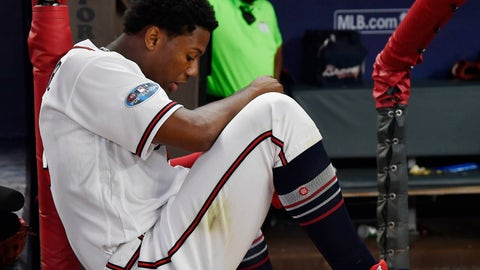 <p>               Atlanta Braves left fielder Ronald Acuna Jr. sits in the dugout as the Los Angeles Dodgers celebrate their win after Game 4 of baseball's National League Division Series, Monday, Oct. 8, 2018, in Atlanta. The Los Angeles Dodgers won 6-2. (AP Photo/John Amis)             </p>