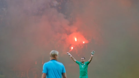 <p>               Serbia's goalkeeper Predrag Rajkovic gestures on the pitch as Romanian fans light flares during the UEFA Nations League soccer match between Romania and Serbia on the National Arena stadium in Bucharest, Romania, Sunday, Oct. 14, 2018. (AP Photo/Vadim Ghirda)             </p>