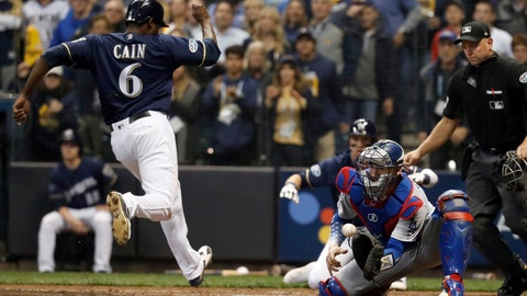 <p>               Milwaukee Brewers' Lorenzo Cain (6) scores a run as Los Angeles Dodgers catcher Yasmani Grandal misses a tag during the third inning of Game 1 of the National League Championship Series baseball game Friday, Oct. 12, 2018, in Milwaukee. (AP Photo/Jeff Roberson)             </p>