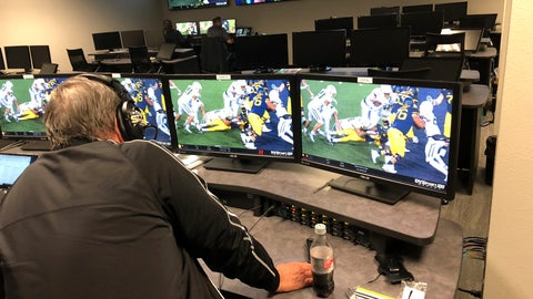 <p>               David Warden, the Big 12's replay coordinator, takes a close look at a play that was initially ruled a touchdown for West Virginia running back Leddie Brown during an NCAA college football game against Baylor, in the conference's centralized replay center in Irving, Texas, Thursday, Oct. 25, 2018. The call was overturned, and the ball placed on the 1-yard line. (AP Photo/Stephen Hawkins)             </p>