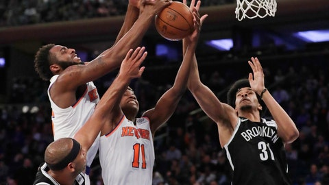<p>               New York Knicks' Mitchell Robinson, left, and Frank Ntilikina, center, and Brooklyn Nets' Jarrett Allen (31) reach for a rebound during the first half of a preseason NBA basketball game Friday, Oct. 12, 2018, in New York. (AP Photo/Frank Franklin II)             </p>