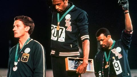 """<p>               FILE - In this Oct. 16, 1968, file photo, U.S. athletes Tommie Smith, center, and John Carlos stare downward as they extend gloved hands skyward in during the playing of the """"Star Spangled Banner"""" after Smith received the gold and Carlos the bronze for the 200 meter run at the Summer Olympic Games in Mexico City. Australian silver medalist Peter Norman is at left. When Smith and Carlos raised their fists 50 years ago at the Mexico City Olympics, they had a captive audience, back in the age when TV was king and the entire audience was rapt. A half-century later, many of the messages our athletes disseminate are every bit as powerful, but the audience is much more distracted.  (AP Photo/File)             </p>"""