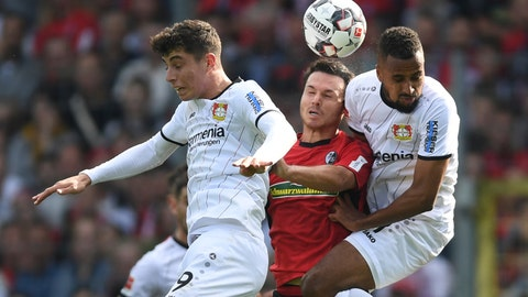 <p>               Leverkusen's Kai Havertz, left, and Jonathan Tah, right, challenge for the ball with Freiburg's Nicolas Hoefler, center, during a German Bundesliga soccer match between SC Freiburg and Bayer 04 Leverkusen in Freiburg, Germany, Sunday, Oct. 7, 2018. (Patrick Seeger/dpa via AP)             </p>