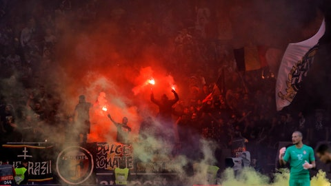 <p>               FILE - In this Oct. 14, 2018 file photo Serbia's goalkeeper Predrag Rajkovic walks on the pitch as Romanian fans light flares during the UEFA Nations League soccer match between Romania and Serbia on the National Arena stadium in Bucharest, Romania. Romania will have to play its next competitive game behind closed doors and its soccer association was fined by UEFA for racist chants and banners and other misconduct of fans at the Nations League game. (AP Photo/Vadim Ghirda, file)             </p>