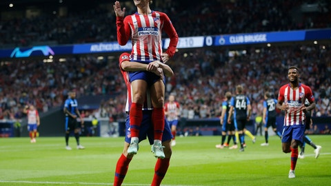 <p>               Atletico forward Antoine Griezmann, front, gestures as he is lifted in the air by Atletico defender Diego Godin, after he scored his side opening goal during a Group A Champions League soccer match between Atletico Madrid and Club Brugge at the Wanda Metropolitano stadium in Madrid, Spain, Wednesday Oct. 3, 2018. (AP Photo/Paul White)             </p>