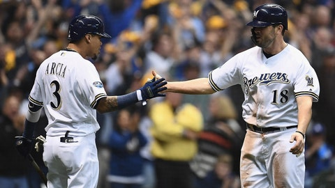 MILWAUKEE, WI - OCTOBER 19:  Mike Moustakas #18 of the Milwaukee Brewers celebrates with his teammate Orlando Arcia #3 after scoring a run off of a single hit by Erik Kratz #15 against Hyun-Jin Ryu #99 of the Los Angeles Dodgers during the first inning in Game Six of the National League Championship Series at Miller Park on October 19, 2018 in Milwaukee, Wisconsin.  (Photo by Stacy Revere/Getty Images)