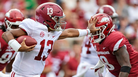 FAYETTEVILLE, AR - OCTOBER 6:  Tua Tagovailoa #13 of the Alabama Crimson Tide runs the ball and stiff arms De'Jon Harris #8 of the Arkansas Razorbacks at Razorback Stadium on October 6, 2018 in Tuscaloosa, Alabama.  The Crimson Tide defeated the Razorbacks 65-31.  (Photo by Wesley Hitt/Getty Images)