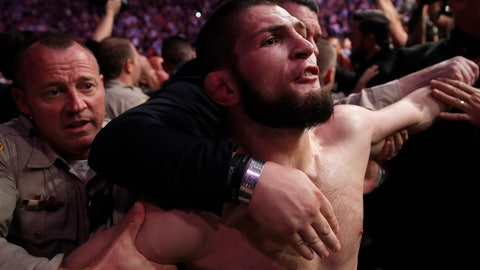 <p>               Khabib Nurmagomedov is held back outside of the cage after fighting Conor McGregor in a lightweight title mixed martial arts bout at UFC 229 in Las Vegas, Saturday, Oct. 6, 2018. Nurmagomedov won the fight by submission during the fourth round to retain the title. (AP Photo/John Locher)             </p>