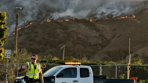 <p>               A police officer directs traffic at a checkpoint in front of an advancing wildfire Thursday, Nov. 8, 2018, near Newbury Park, Calif. The Ventura County Fire Department has also ordered evacuation of some communities in the path of the fire, which erupted a few miles from the site of Wednesday night's deadly mass shooting at a Thousand Oaks bar. (AP Photo/Richard Vogel)             </p>