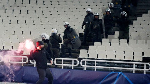 <p>               A fan throws a flare towards Ajax supporters during a Group E Champions League soccer match between AEK Athens and Ajax at the Olympic Stadium in Athens, Tuesday, Nov. 27, 2018. (AP Photo/Thanassis Stavrakis)             </p>