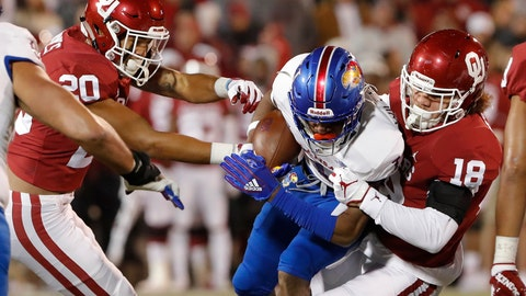 <p>               Kansas running back Pooka Williams Jr., center, is tackled by Oklahoma safety Robert Barnes, left, and linebacker Curtis Bolton, right, during the first half of an NCAA college football game in Norman, Okla., Saturday, Nov. 17, 2018. (AP Photo/Alonzo Adams)             </p>