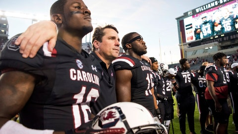 <p>               FILE - In this Saturday, Oct. 13, 2018, file photo, South Carolina head coach Will Muschamp, second from left, puts his arms around Rashad Fenton (16) and Aaron Sterling (15) after an NCAA college football game against Texas A&M in Columbia, S.C. Hurricane Florence and the looming bowl season has South Carolina and Virginia Tech closing their football seasons against teams that were never on their schedule. (AP Photo/Sean Rayford, File)             </p>