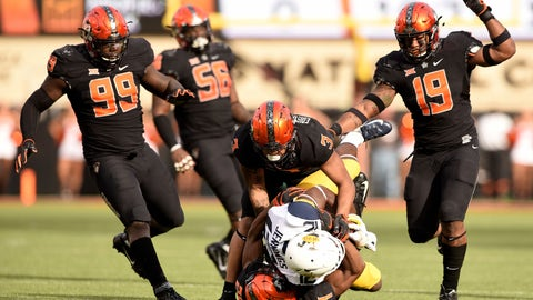 <p>               Oklahoma State defensive tackle Trey Carter (99) and offensive lineman Larry Williams (56) watch as teammates Kenneth Edison-McGruder (3), linebacker Justin Phillips (19) and safety Jarrick Bernard (24) stop the advance of West Virginia wide receiver Gary Jennings Jr during the first half of an NCAA college football game in Stillwater, Okla., Saturday, Nov. 17, 2018. Oklahoma State upset West Virginia 45-41. (AP Photo/Brody Schmidt)             </p>