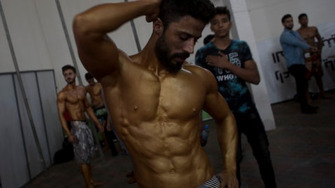 <p>               In this Friday, Oct. 26, 2018 photo, a Palestinian bodybuilder prepares himself before giving a performance during a local bodybuilding competition, in Gaza City. While thousands of Palestinians gather at the border with Israel for a new weekly protest on a recent Friday, hundreds of others packed a sports hall in Gaza City for a different type of gathering -- a bodybuilding competition. (AP Photo/Khalil Hamra)             </p>