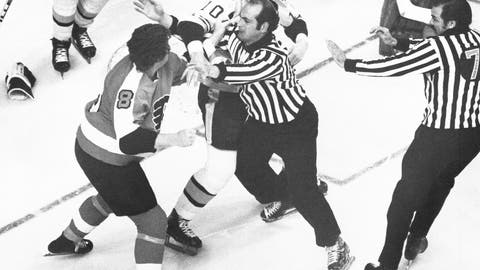 """<p>               FILE - In this May 16, 1974, file photo, Philadelphia Flyers, Dave Schultz (8) left, tries to swing around linesman John D'Amico, center, to get to Boston Bruins Carol Vadnais in a first period fight during an NHL playoff game in Boston. Both players were penalized for fighting. In the 1970s, the Flyers had guys like Dave """"The Hammer"""" Schultz, Bob """"The Hound"""" Kelly and Andre """"Moose"""" Dupont around to not just beat opponents but beat them up, too. More than 40 years later, the Flyers still carry the """"Bullies"""" nickname but are hardly bullying anyone: They're one of only two teams in the NHL without a fight a quarter of the way through the season. (AP Photo/File)             </p>"""