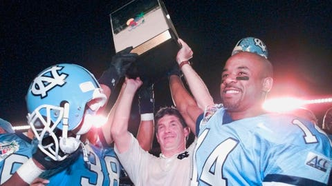<p>               FILE - In this Dec. 30, 1995, file photo, North Carolina head coach Mack Brown hoists the trophy in the air as he's surrounded by players Eric Thomas(38) and Marcus Wall (14) after they defeated Arkansas 20-10 in the Carquest Bowl NCAA college football game in Miami. Two people with knowledge of the situation say North Carolina is negotiating with Mack Brown on a deal to return to Chapel Hill as its next football coach. The people spoke to The Associated Press on condition of anonymity Monday, Nov. 26, 2018, because the school hasn't publicly commented on its coaching search. One of the people says that the deal is being finalized. (AP Photo/Hans Deryk, File)             </p>
