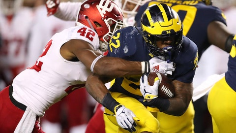 ANN ARBOR, MICHIGAN - NOVEMBER 17:  Karan Higdon #22 of the Michigan Wolverines battles for yards past Marcelino Ball #42 of the Indiana Hoosiers during a second half run at Michigan Stadium on November 17, 2018 in Ann Arbor, Michigan. Michigan won the game 31-20. (Photo by Gregory Shamus/Getty Images)