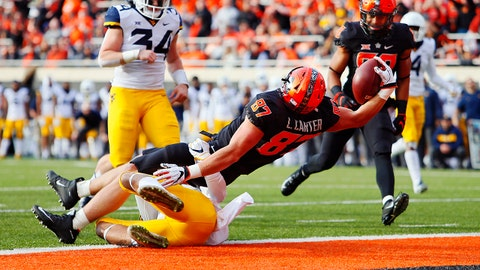STILLWATER, OK - NOVEMBER 17:  Tight end Logan Carter #87 of the Oklahoma State Cowboys falls backward into the end zone for a touchdown against safety Kenny Robinson Jr. #2 of the West Virginia Mountaineers in the second quarter on November 17, 2018 at Boone Pickens Stadium in Stillwater, Oklahoma. (Photo by Brian Bahr/Getty Images)