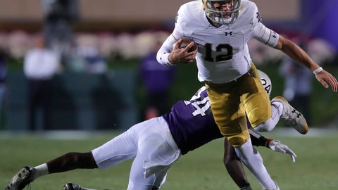 <p>               Notre Dame's Ian Book, right, breaks away from a tackle by Northwestern's Montre Hartage during the first half of an NCAA college football game Saturday, Nov. 3, 2018, in Evanston, Ill. (AP Photo/Jim Young)             </p>