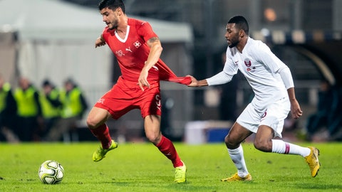 <p>               FILE - In this file photo taken on , Wednesday, Nov. 14, 2018, Switzerland's Loris Benito, left, is challenged by Qatar's Abdulaziz Hatem during an international friendly soccer match between Switzerland and Qatar at the Cornaredo stadium in Lugano, Switzerland. Exactly four years from now (Nov. 21), Qatar will be kicking off the World Cup in its own country, in front of 80,000 fans at Lusail Stadium, with around 300 million more watching on television. (Ennio Leanza/Keystone via AP)             </p>