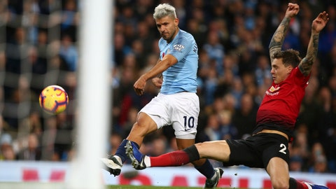 <p>               Manchester City's Sergio Aguero shoots past Manchester United's Victor Lindelof to score his team's second goal during the English Premier League soccer match between Manchester City and Manchester United at the Etihad stadium in Manchester, England, Sunday, Nov. 11, 2018. (AP Photo/Dave Thompson)             </p>
