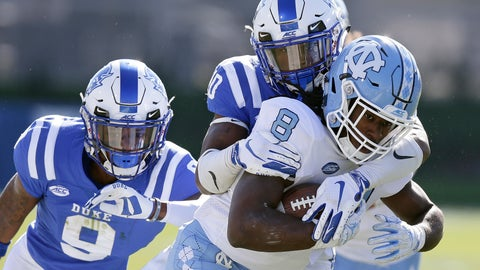 <p>               North Carolina's Michael Carter (8) runs the ball while Duke's Jeremy McDuffie (9) and Marquis Waters move in for the tackle during the first half of an NCAA college football game in Durham, N.C., Saturday, Nov. 10, 2018. (AP Photo/Gerry Broome)             </p>