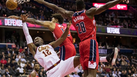 <p>               Cleveland Cavaliers guard David Nwaba (12) tries to shoot past Washington Wizards forward Kelly Oubre Jr. (12) and center Ian Mahinmi (28), from France, during the first half of an NBA basketball game Wednesday, Nov. 14, 2018, in Washington. (AP Photo/Alex Brandon)             </p>
