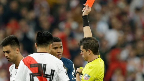 <p>               Referee Andres Cunha, of Uruguay, shows a red card to Wilmar Barrios of Argentina's Boca Juniors, center in blue, during a Copa Libertadores final soccer match between River Plate and Boca Juniors at the Santiago Bernabeu stadium in Madrid, Spain, Sunday, Dec. 9, 2018. (AP Photo/Armando Franca)             </p>