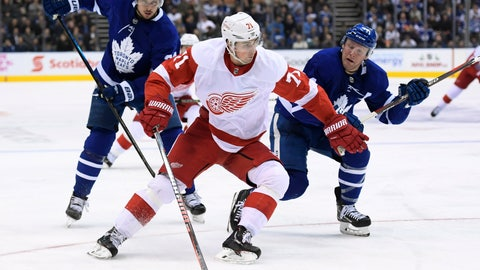 <p>               Detroit Red Wings center Dylan Larkin (71) moves past Toronto Maple Leafs defenseman Morgan Rielly (44) as Maple Leafs center Auston Matthews (34) watches during the third period of an NHL hockey game Thursday, Dec 6, 2018, in Toronto. (Nathan Denette/The Canadian Press via AP)             </p>