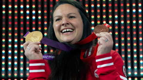 <p>               Canadian weightlifter Christine Girard holds up the gold and bronze Olympic medals she was awarded during a ceremony in Ottawa, Monday, Dec. 3, 2018. Girard was awarded the London 2012 gold and Beijing 2008 bronze medals after the International Olympic Committee disqualified athletes from the 2008 and 2012 Olympic games.  (Adrian Wyld/The Canadian Press via AP)             </p>
