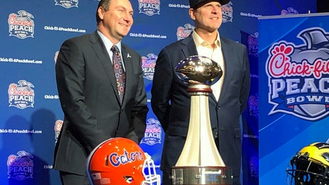 <p>               Florida Head Coach Dan Mullen, left, and Michigan Head Coach Jim Harbaugh stand alongside the George P. Crumbley Trophy, in Atlanta, GA., Friday, Dec. 28, 2018. The teams will play in the Peach Bowl Saturday. (AP Photo/ Charles Odum)             </p>