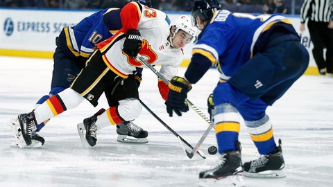 <p>               Calgary Flames' Johnny Gaudreau (13) falls between St. Louis Blues' Brayden Schenn (10) and Jay Bouwmeester, right, during the third period of an NHL hockey game Sunday, Dec. 16, 2018, in St. Louis. (AP Photo/Jeff Roberson)             </p>